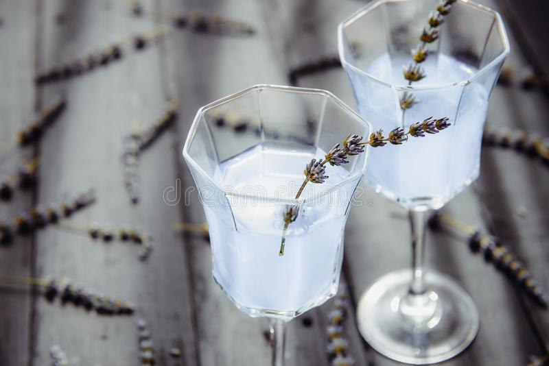 Close up Fresh lavender lemonade with flowers in beautiful glasses on dark wooden table in back light. Detox water. Summer drink. Diet cocktail. Selective stock photography