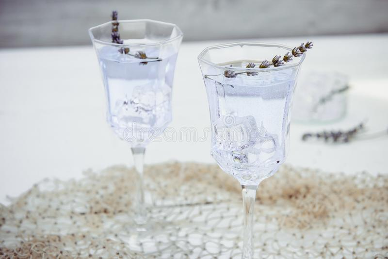 Close up Fresh lavender lemonade with flowers and ice cubes in beautiful glasses on white wooden table. Detox water. Summer drink. Diet cocktail. Selective stock images