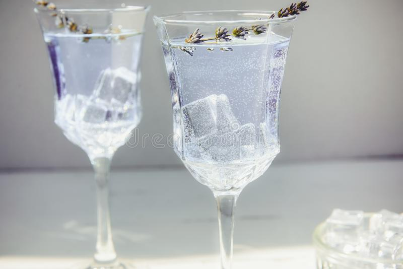 Close up Fresh lavender lemonade with flowers and ice cubes in beautiful glasses on white wooden table. Detox water. Summer drink. Diet cocktail. Selective royalty free stock images