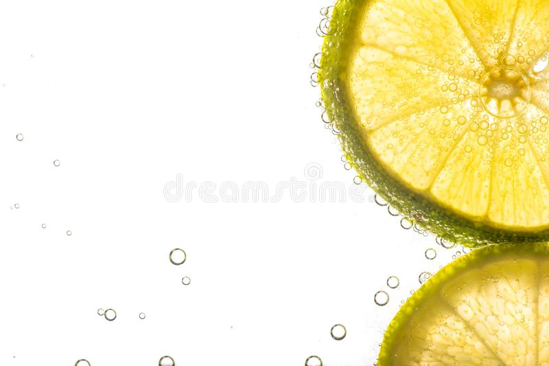 Close up fresh lime sliced in soda. Or water bubbles, isolated on white background stock image