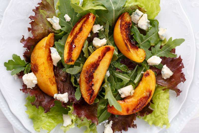 Close-up of fresh mixed salad. Lettuce and arugula leaves with grilled peach and blue cheese stock photos