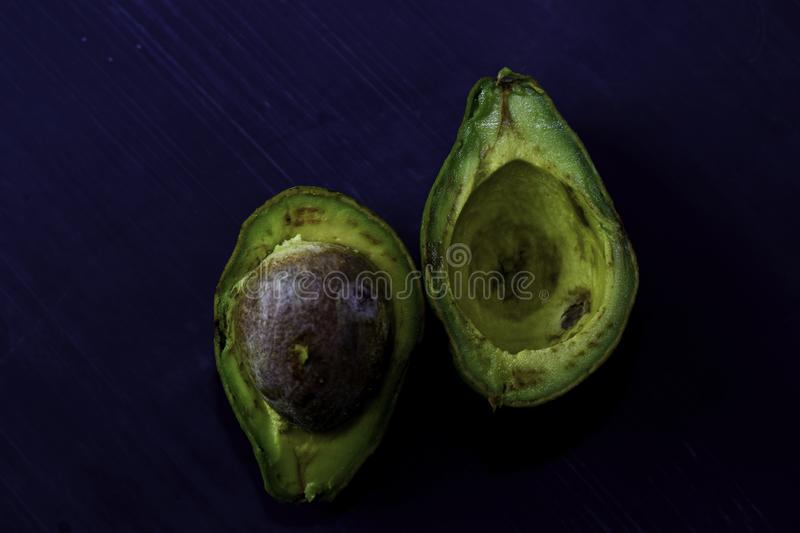 Close up fresh organic avocado halves on old black table background. Healthy food concept royalty free stock photography