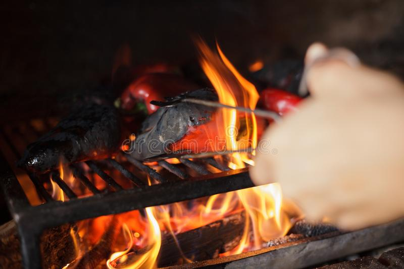 Preparing traditional Balkan`s delicacy Ajvar, grilling paprika on an open flame. Close-up of fresh organic red paprika being grilled on open flame. Preparing royalty free stock photography