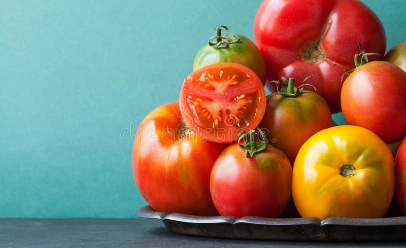 Close up fresh organic tomatoes on a tray. Variety tomato vegetables, different size red yellow pink green color. Green royalty free stock photography