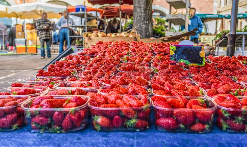 Close up fresh red strawberry berries in plastic containers in wooden box on retail display of farmers market, high royalty free stock images