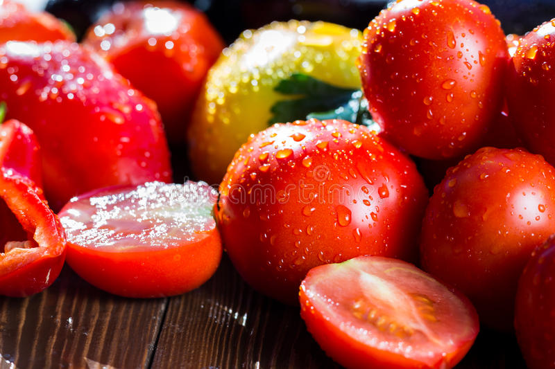 Close-up of fresh, ripe tomatoes on wood background.Group of tom. Atoes. Red and yellow tomatoes, tomatoes in drops of water royalty free stock photography