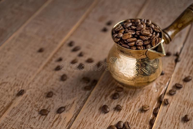 Close up of fresh roasted coffe beans in  cezve traditional turkish coffee pot on wooden table.  royalty free stock images