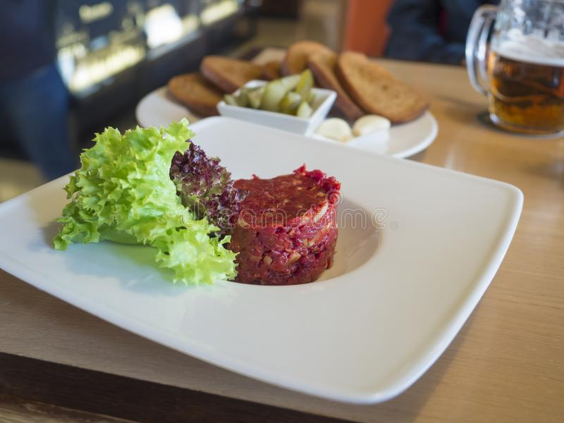 Close up fresh Steak tartare with lettuce leaves on white plate,. Toasted bread, garlick, pickles and beer in background, selective focus royalty free stock images