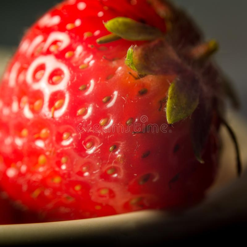 Close up of fresh strawberry`s. Close up bowl of vibrant red strawberry`s with limited focus.  The foreground strawberry has a small stalk and green leaves stock images
