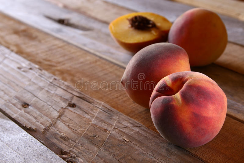 close up of fresh sweet peaches on rustic wooden table stock images