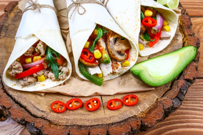 Close up of fresh tacos with avocado, salsa and lime in a flour tortilla on a wooden stump royalty free stock images