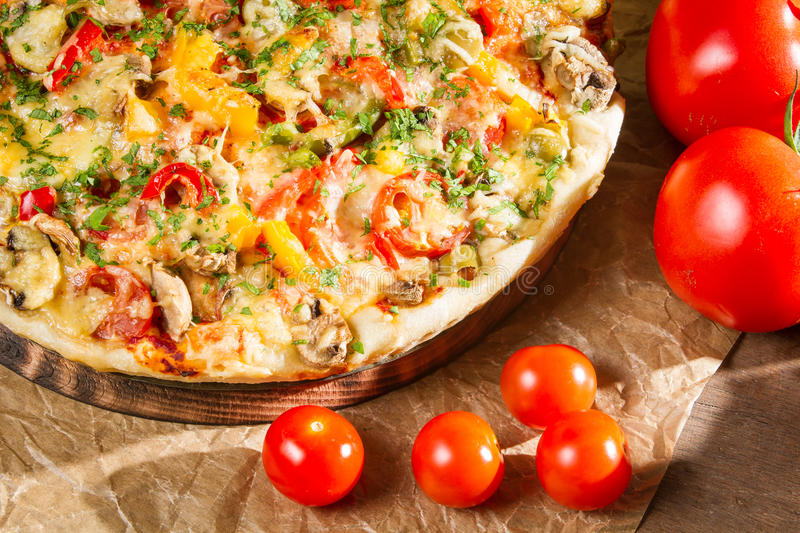 Close-up of fresh tomatoes and baked pizzas stock photo