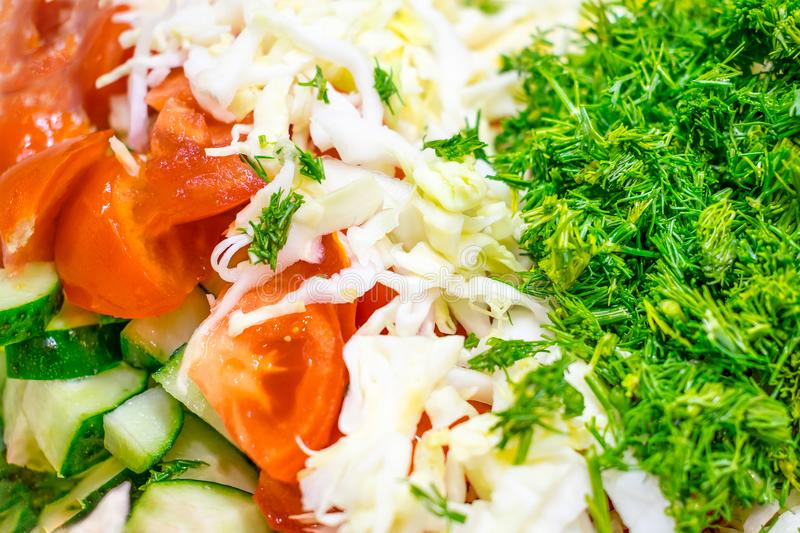Close-up of Fresh vegetable mixed salad. Sliced cucumbers, tomatoes, cabbage and greens dill. Ingredients for salad, the process royalty free stock image