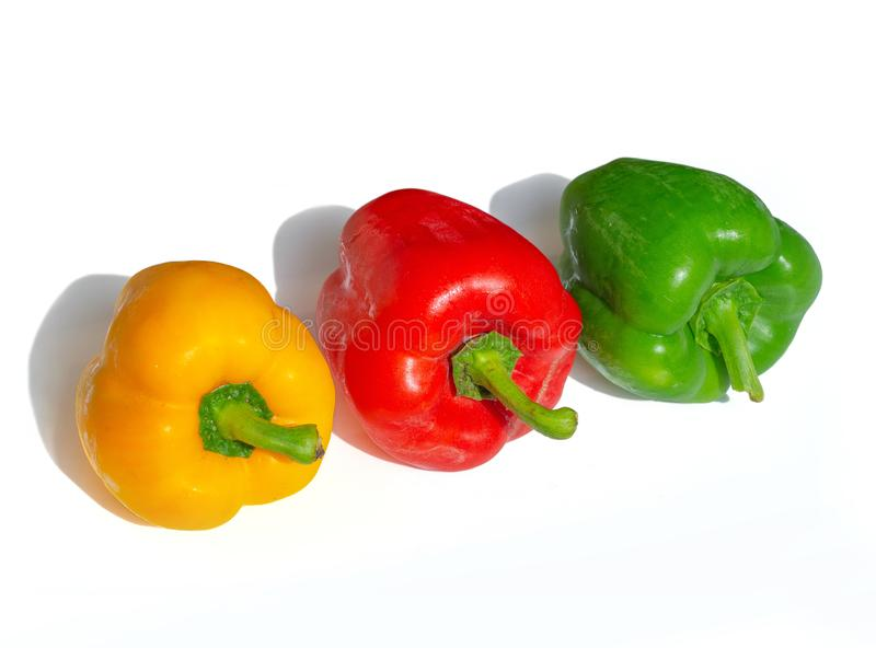 Close-up fresh vegetables Three sweet Red, Yellow, Green Peppers on white background. Top view royalty free stock photos