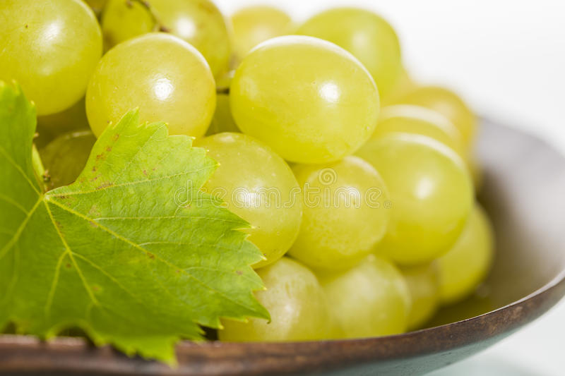 Close up of fresh white grapes on brown plate. Close up of a bunch of fresh white grapes with leaf on brown plate royalty free stock images