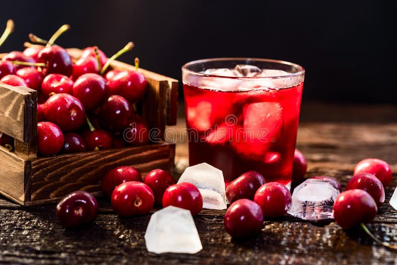 Fresh cherries in a wooden box, ice, cherry juice royalty free stock image