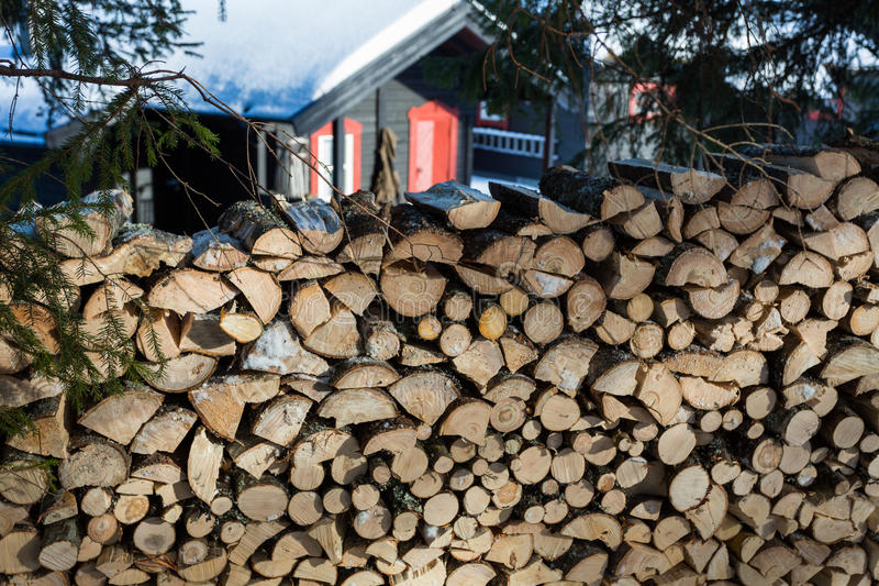 Close up of freshly chopped wood pile with a cabin in the background royalty free stock images