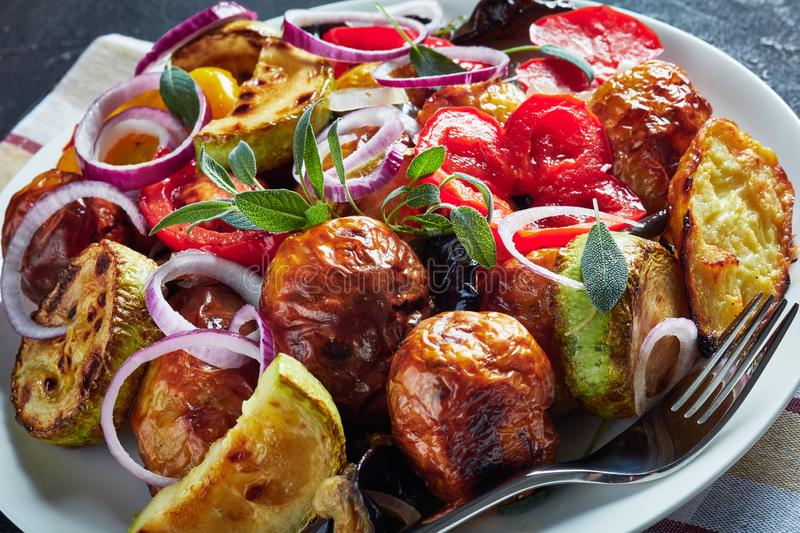 close-up of freshly roasted in an oven hot vegetables - potatoes, eggplants, zucchini, tomatoes, bell peppers on a white platter stock photos