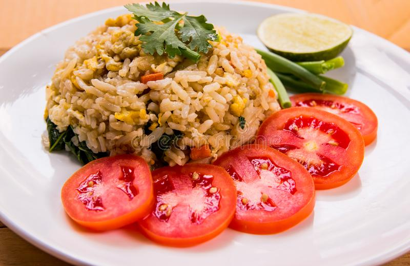 Close up fried rice with eggs and pork served with fresh tomato slice, spring onions and lemon slice on white plate on the table. Fried rice with eggs and pork royalty free stock photos