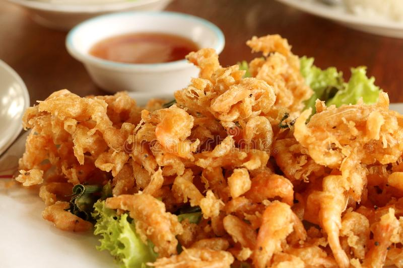 Close up fried small shrimp with sauce on wooden table in the restaurant, Thai food.  royalty free stock images