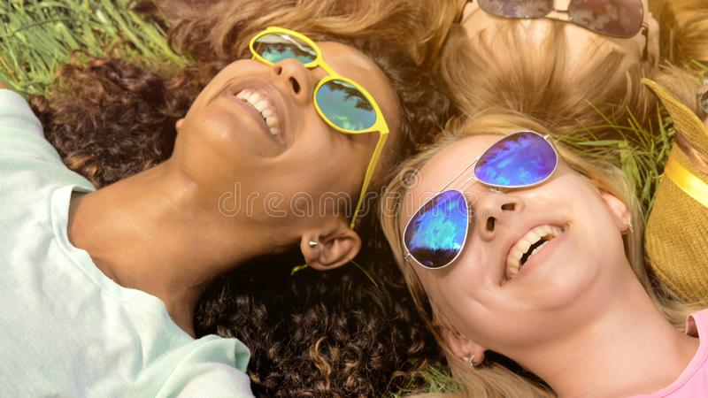 Close-up of friends faces, happy girls lying on grass, multiracial friendship stock photography