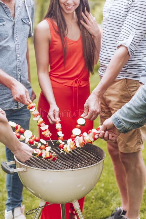 Close-up of friends grilling shashliks during garden party in the summer. Photo concept stock image