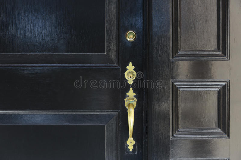 Close up of front door with door handle and two locks royalty free stock photography