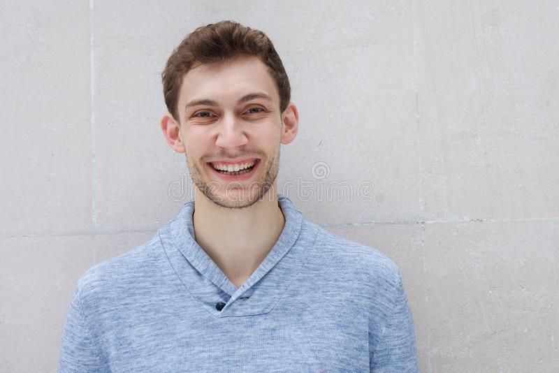 Close up front of happy young man smiling by wall royalty free stock photo