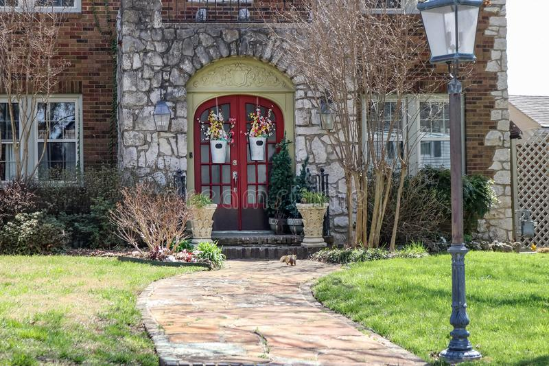 Close-up of front of house with beautiful flowers on double doors n early springtime with frisky squirrel running up the sidewalk royalty free stock photos