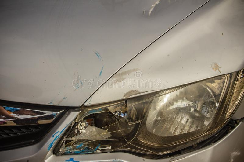 Close-up front of new silver car distorted by accident. Crashed. New silver car severely damaged and needs help for move to the garage to repair and call to stock images
