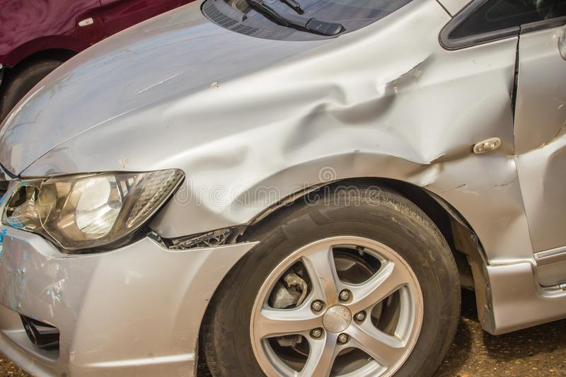 Close-up front of new silver car distorted by accident. Crashed. New silver car severely damaged and needs help for move to the garage to repair and call to royalty free stock photo