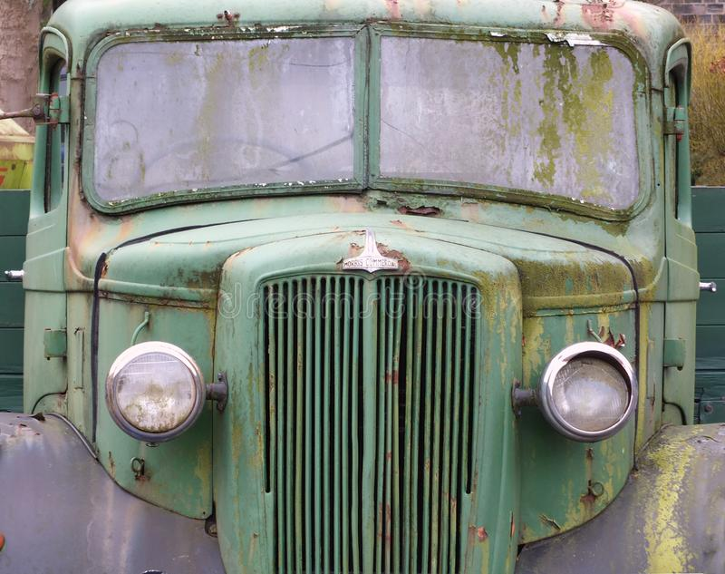 a close up of the front of an old abandoned Austin Commercial LC3 rusting green truck covered in moss. The LC series was built in royalty free stock images