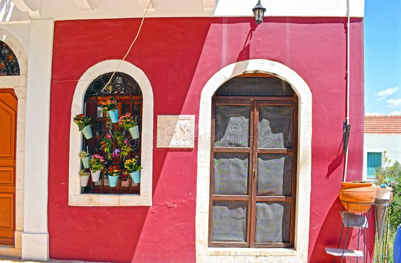 Close up of a beautifully decorated Greek house. A close up of the front of a red and white Greek house front with the arch shaped window covered in pots of royalty free stock photos