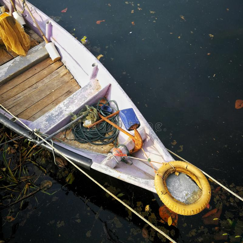 Close-up of front side of small fisherman boat moored in port. Small row boat floating. royalty free stock image