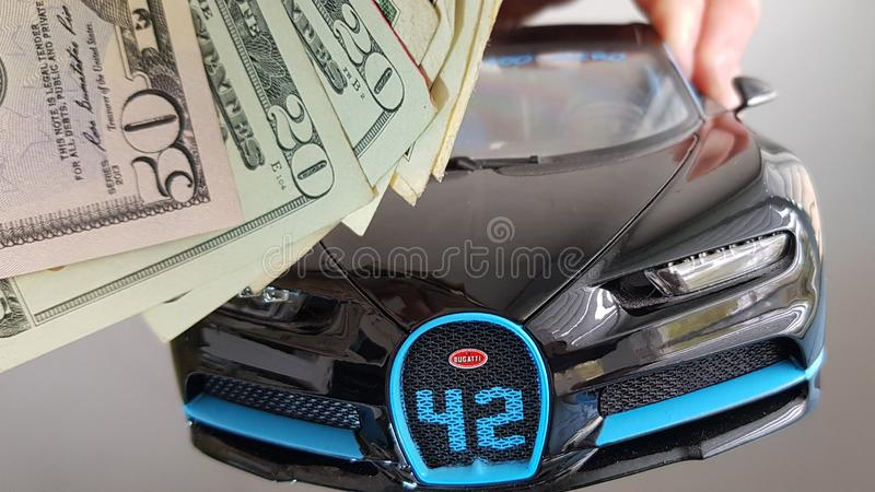 Close-up of front view Black Bugatti Chiron car metal toy flying in the air on white background in human hand with group of americ. Rishon lezion, Israel - march stock photography