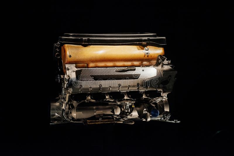 A close up front view of car detail: internal combustion engine with orange part isolated on the black background stock image