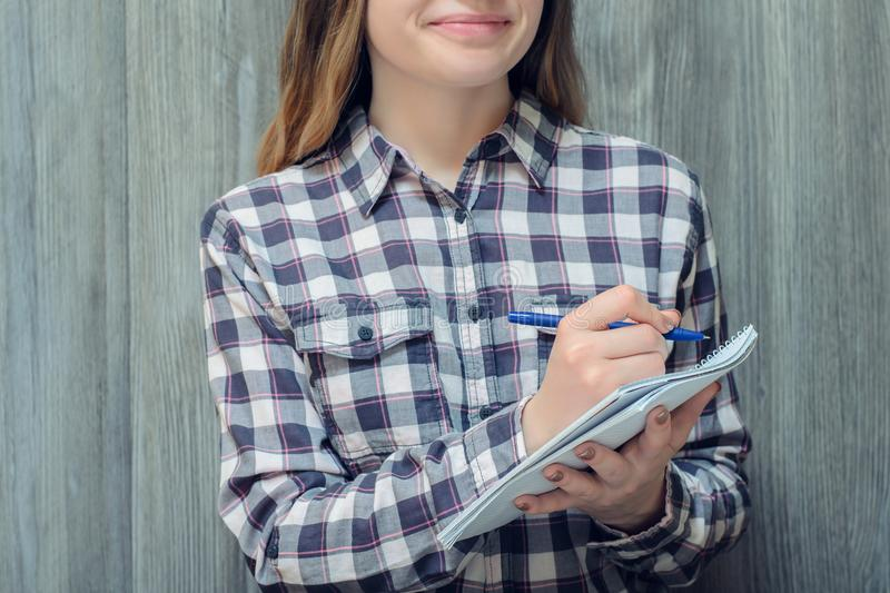 Close up front view cropped portrait of charming nice beautiful smiling happy cheerful young lady woman girl writing essay portrai royalty free stock images