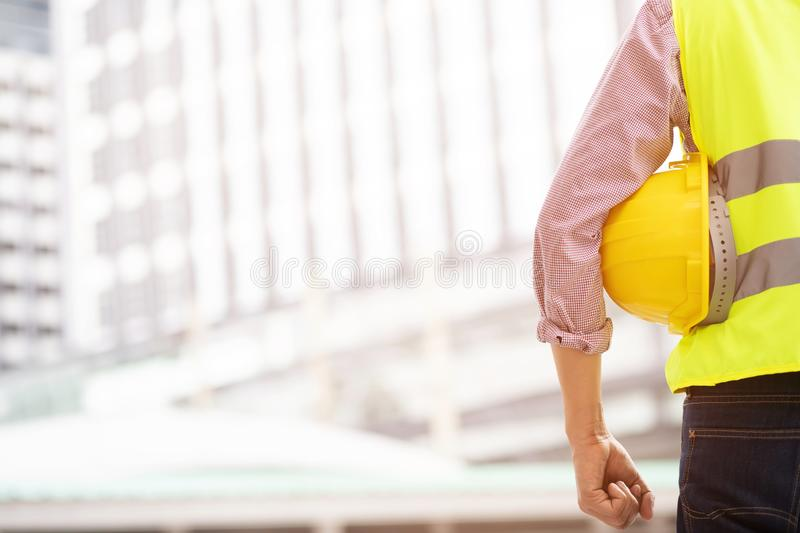 Close up front view of engineering male construction worker holding roll paper royalty free stock photo