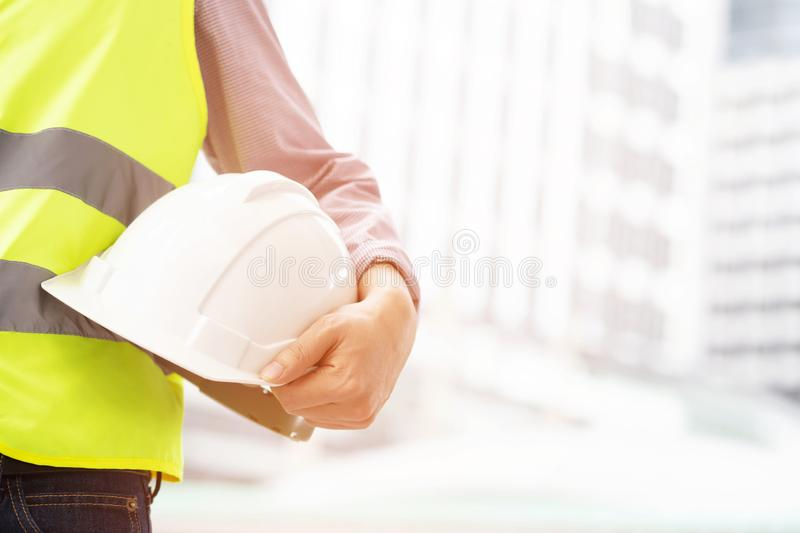 Close up front view of engineering male construction worker holding safety white helmet stock photography