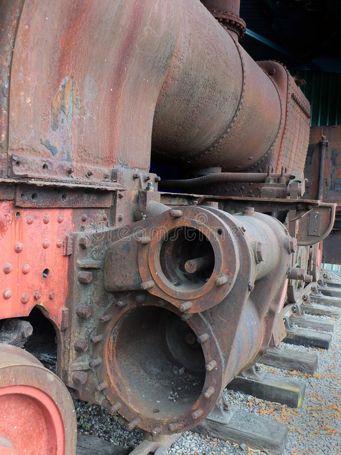 Close up front view of an old abandoned rusting steam locomotive with wrecked cylinders on railway tracks stock photos