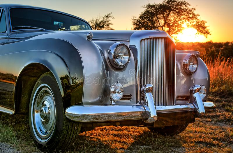 Close up front view of vintage luxery limousine with sunset behind. 1962 Bentley front view in the fading light of sunset with chrome fender, headlights and royalty free stock images