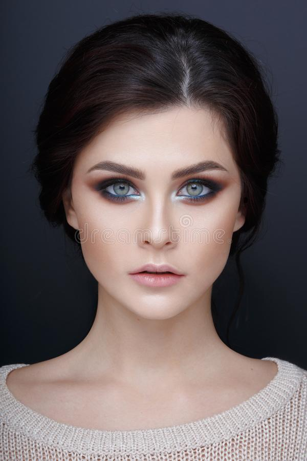 Close up portrait of a beautyful girl with perfect makeup. Face of a beautiful girl,  on a gray background. royalty free stock images