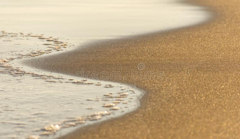 A close up of frothy waves on a stormy day against the golden sandy beach. Copy Paste. Nature stock photo