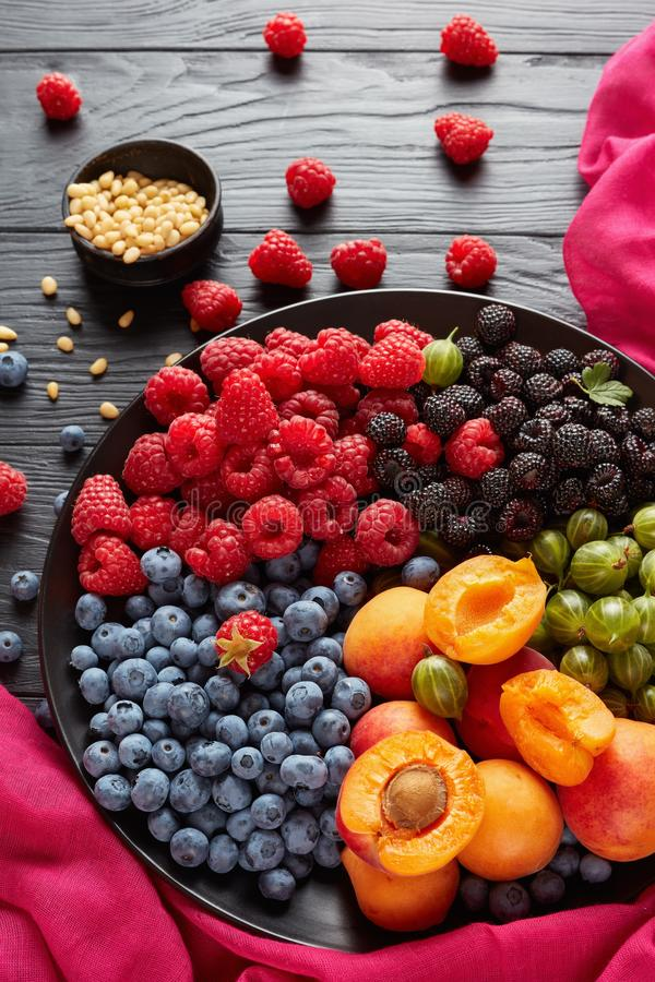 Close-up of Fruit and berries salad. Close-up of Fruit and berries platter with fresh organic gooseberry, red and black raspberry, blueberry, apricot slices on a stock image