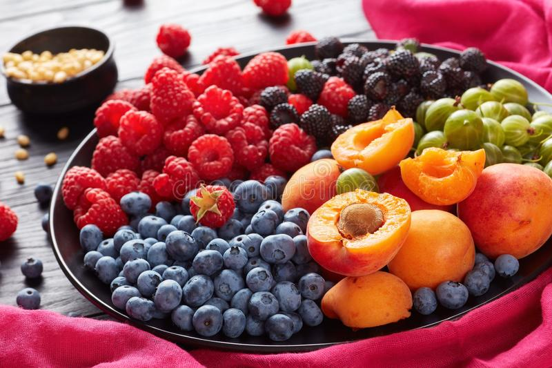 Close-up of Fruit and berries salad. With fresh organic gooseberry, red and black raspberry, blueberry, apricot slices on a black plate on a wooden table with stock photography