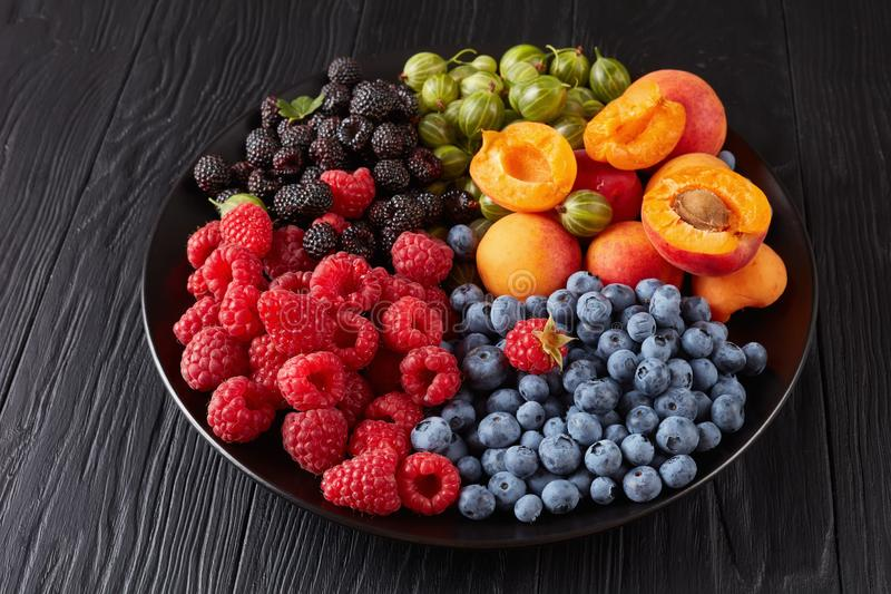 Close-up of Fruit and berries salad. Of fresh organic gooseberry, red and black raspberry, blueberry, apricot slices on a black plate on a wooden table royalty free stock photography