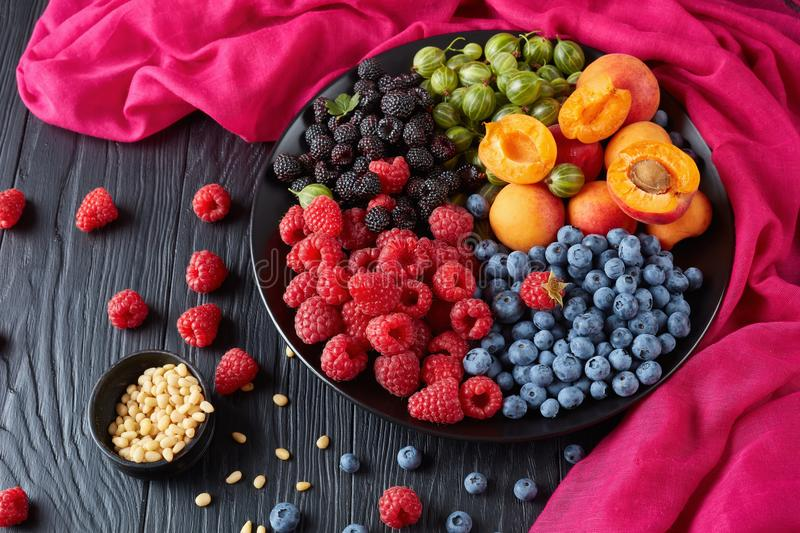 Close-up of Fruit and berries salad. With fresh organic gooseberry, red and black raspberry, blueberry, apricot slices on a black plate on a wooden table with royalty free stock image