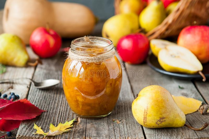 Close up fruit jam and fresh yellow ripe pears, red apples and pumpkin on the old rustic wooden table. Autumn harvest still life c royalty free stock images