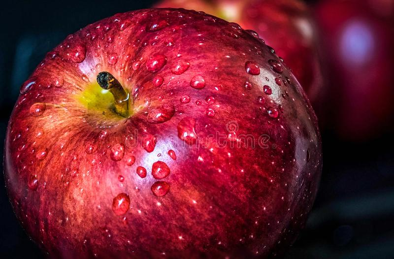 Close-up fruit of water droplet of freshness red apple with black color for the background royalty free stock images