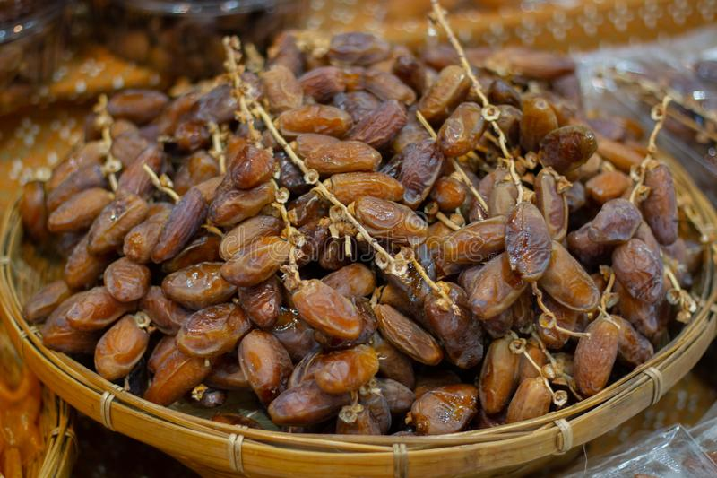 Close up fruits of date palm on the basket. For sale to customer stock image